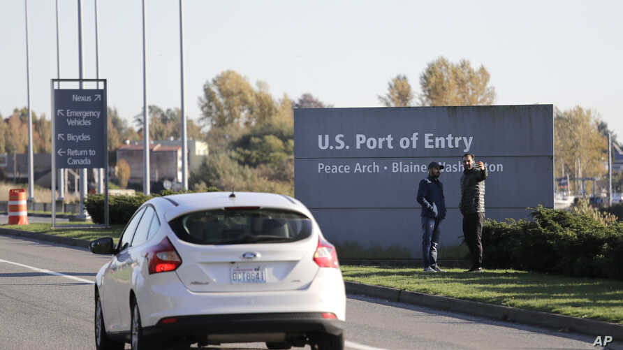 FILE - In this Oct. 9, 2019, file photo, pedestrians take a photo at an entry sign as traffic enters the United States from…