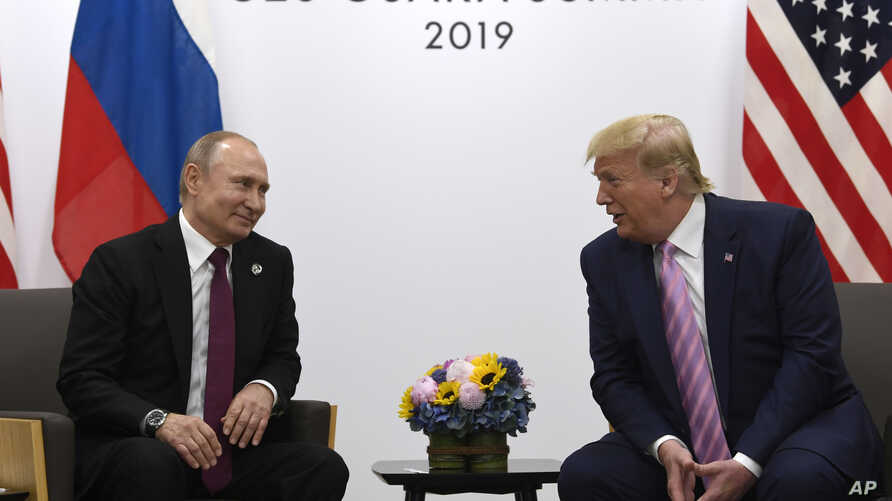 FILE - In this June 28, 2019, file photo, President Donald Trump, right, meets with Russian President Vladimir Putin during a…