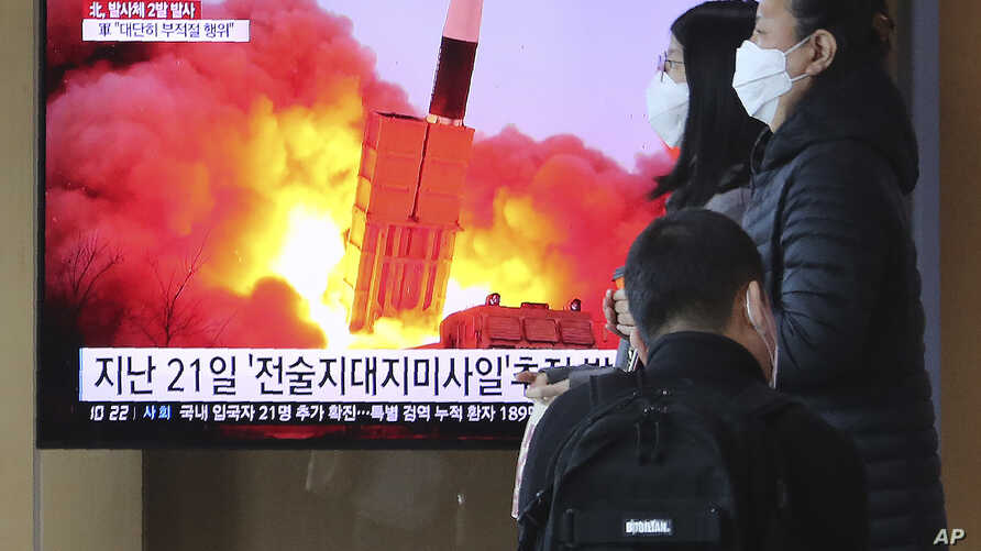 People pass by a TV screen showing a file image of North Korea's missile launch during a news program at the Seoul Railway…