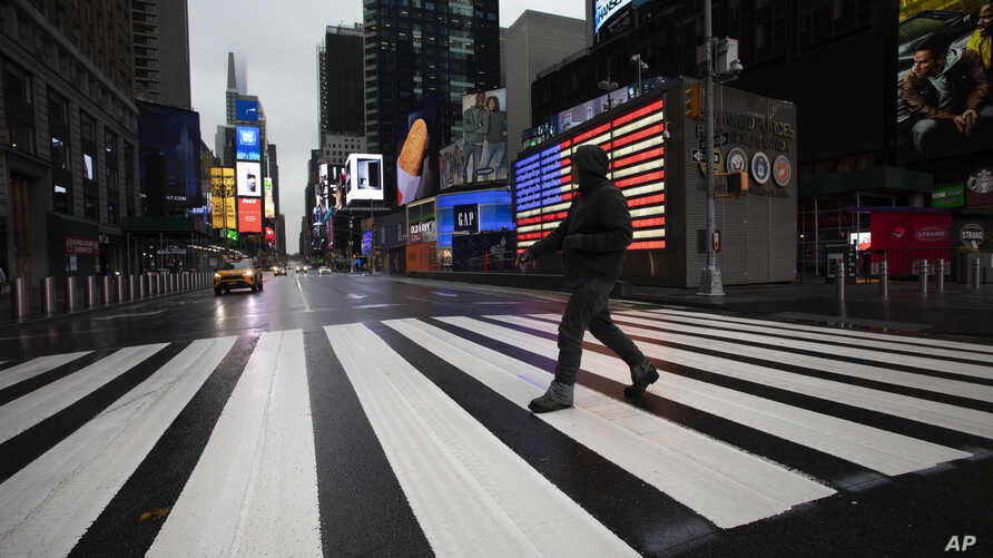 A man crosses the street in a nearly empty Times Square, which is usually very crowded on a weekday morning, Monday, March 23,…