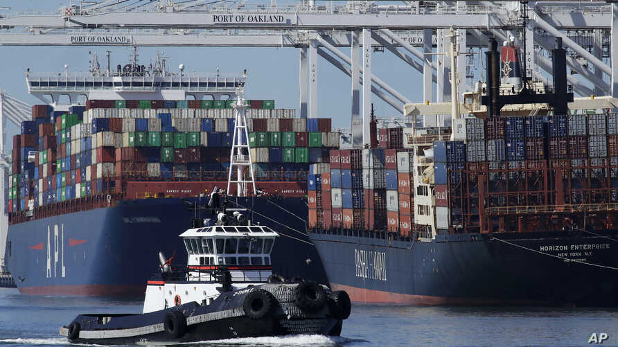 A tugboat passes container ships being unloaded at the Port of Oakland on Wednesday, March 4, 2020, in Oakland, Calif. (AP…