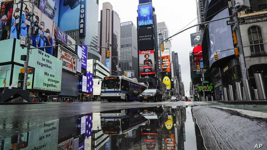 Vehicles move through a nearly empty Times Square during the coronavirus pandemic, Saturday, May 23, 2020, in New York. (AP…