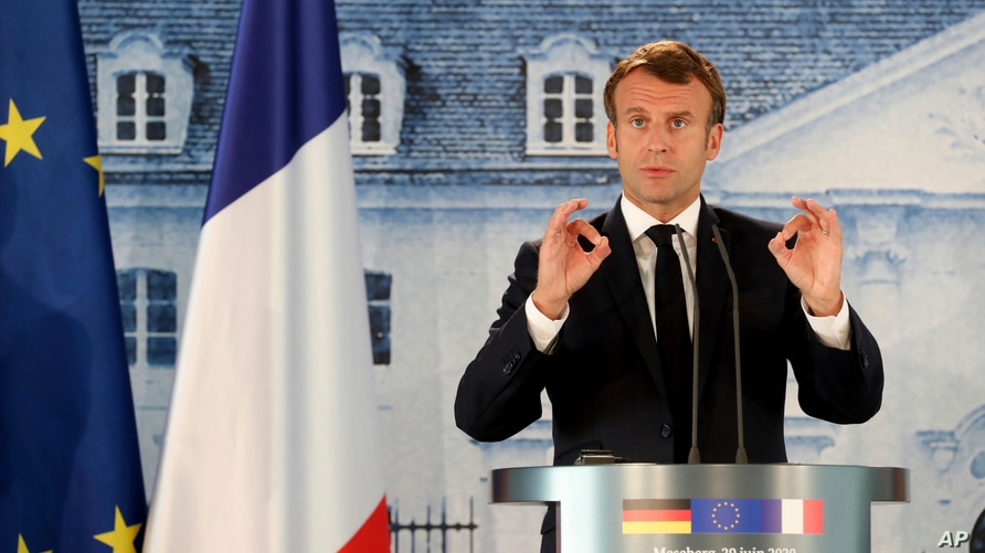 French President Emmanuel Macron gestures as he gives a press conference, at the German government's guest house Meseberg…