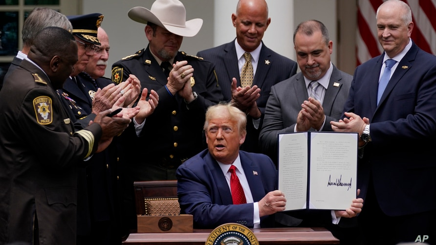 Law enforcement officials applaud after President Donald Trump signed an executive order on police reform, in the Rose Garden…