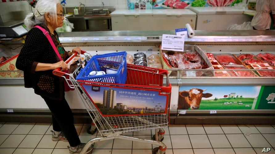 A woman pushes her shopping cart past a display of domestically produced Chinese beef at a supermarket in Beijing, Friday, May…