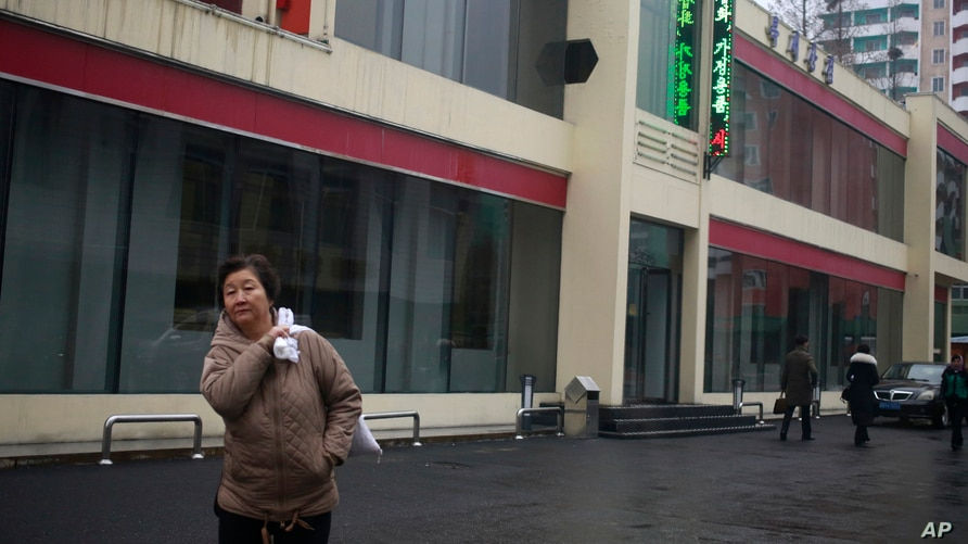 "In this Dec. 21, 2018, photo, a North Korean woman walks outside Bugsae Shop, also known as the ""Singapore Shop,"" in Pyongyang,…"