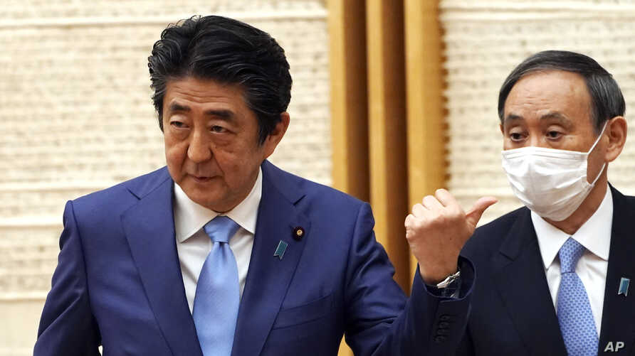 Japan's Prime Minister Shinzo Abe, left, gestures as Chief Cabinet Secretary Yoshihide Suga looks in at the end of a press…