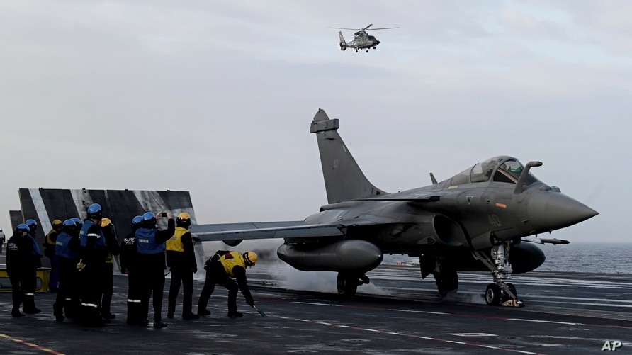 Staff look at a Rafale jet fighter about to take off the French aircraft carrier Charles de Gaulle at sea, off the coast of the…