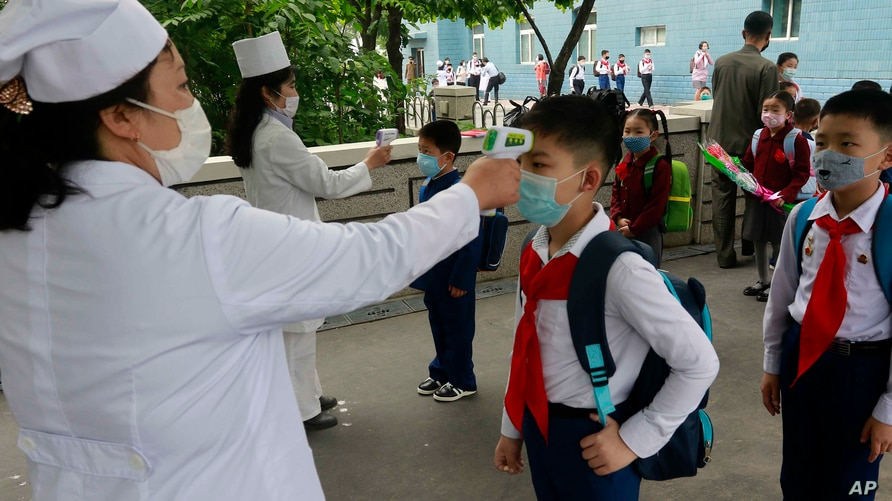 Kim Song Ju Primary school students have their temperatures checked before entering the school in Pyongyang, North Korea,…