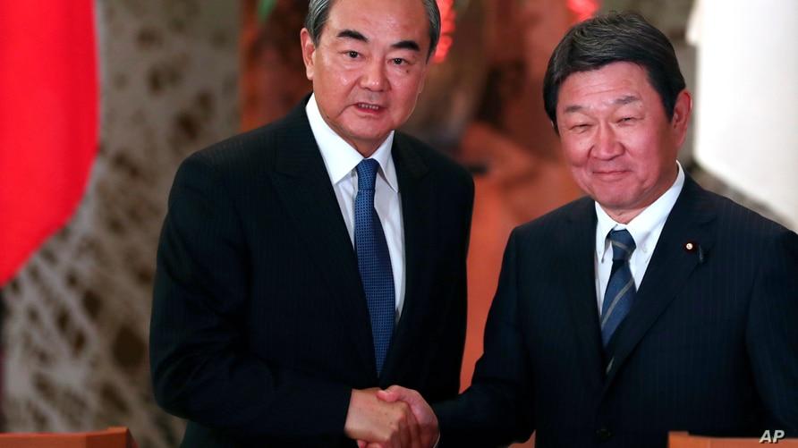 Japan's Foreign Minister Toshimitsu Motegi, right, and his Chinese counterpart Wang Yi  shake hands after giving a press…