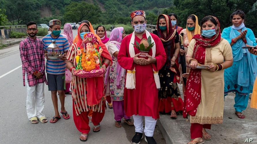 Devotees wearing masks as precaution against the coronavirus walk carrying an idol of Hindu god Ganesha to immerse in a water…