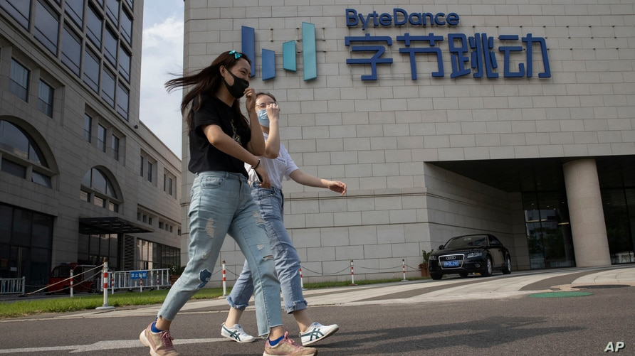 Women wearing masks to prevent the spread of the coronavirus chat as they pass by the ByteDance headquarters in Beijing, China…