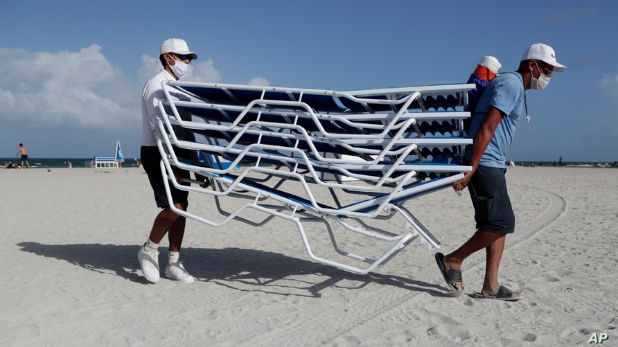 Workers remove chairs from the beach in preparation for Hurricane Isaias, Friday, July 31, 2020, in Miami Beach, Fla…