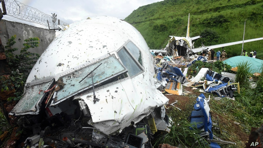 People stand by the debris of the Air India Express flight that skidded off a runway while landing in Kozhikode, Kerala state,…