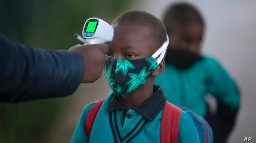 A pupil's temperature is checked on returning to school in Johannesburg, Tuesday July 7, 2020, as more learners were permitted…