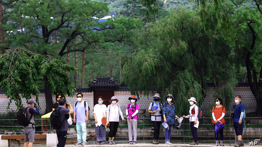Visitors wearing face masks to help protect against the spread of the coronavirus pose to take pictures at the Gyeongbok Palace…