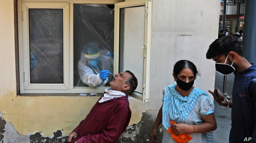 A health worker takes a nasal swab sample to test for COVID-19 in New Delhi, India, Saturday, Sept. 5, 2020. India's…
