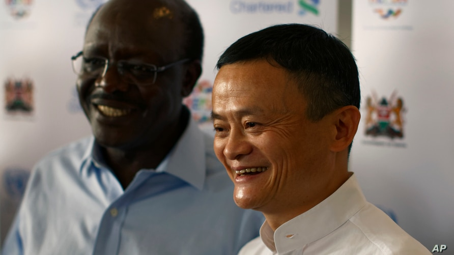 Chinese business magnate, founder and executive chairman of the e-commerce Alibaba Group Jack Ma, right, poses for photos with…
