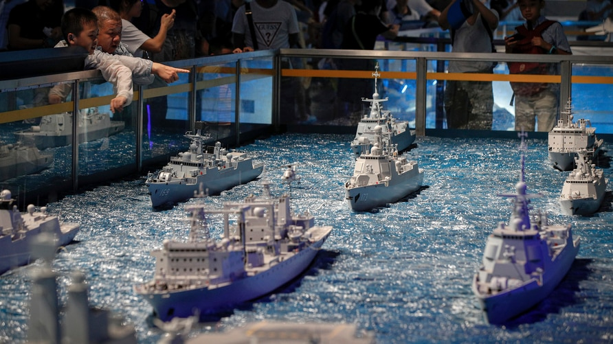 Visitors look at models of Chinese navy frigates on display at the military museum in Beijing, Thursday, Aug. 1, 2019. China…
