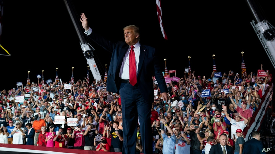 President Donald Trump waves as he walks off after speaking at a campaign rally at Orlando Sanford International Airport,…