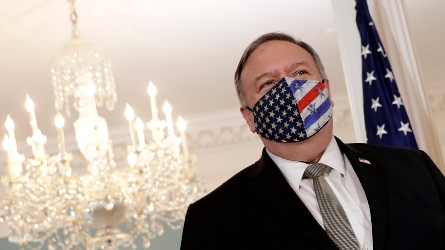 Secretary of State Mike Pompeo wears a face mask before meeting with Romania's Foreign Minister Bogdan Aurescu at the State…