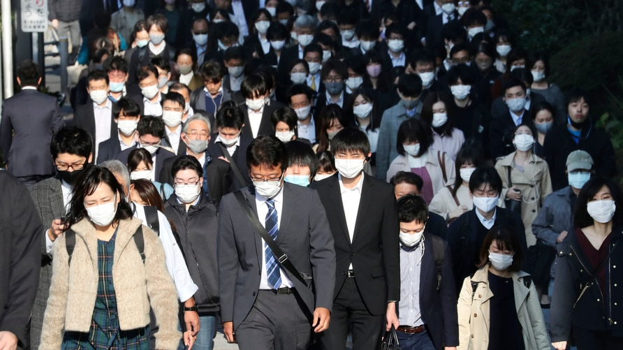 Commuters wearing face masks to protect against the spread of the coronavirus walk on a street in Tokyo, Tuesday, Nov. 17, 2020…