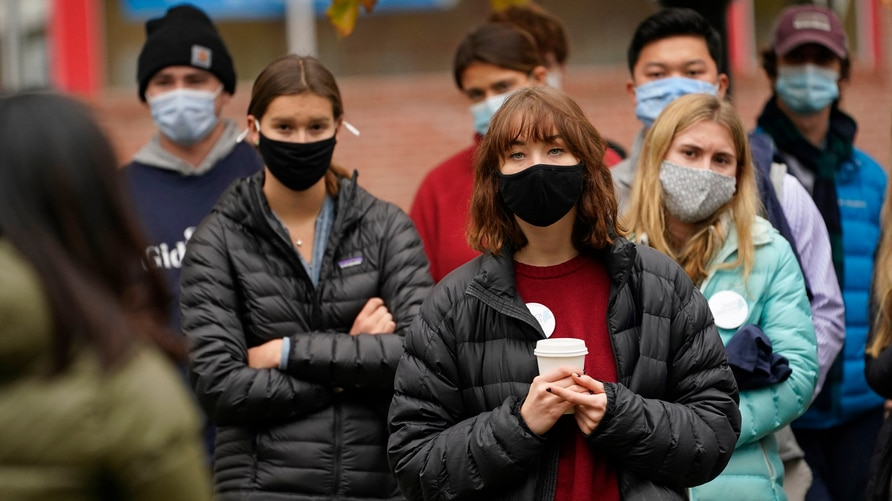 Students from Bowdoin College wear masks to help prevent the spread of the coronavirus while attending a campaign event for…