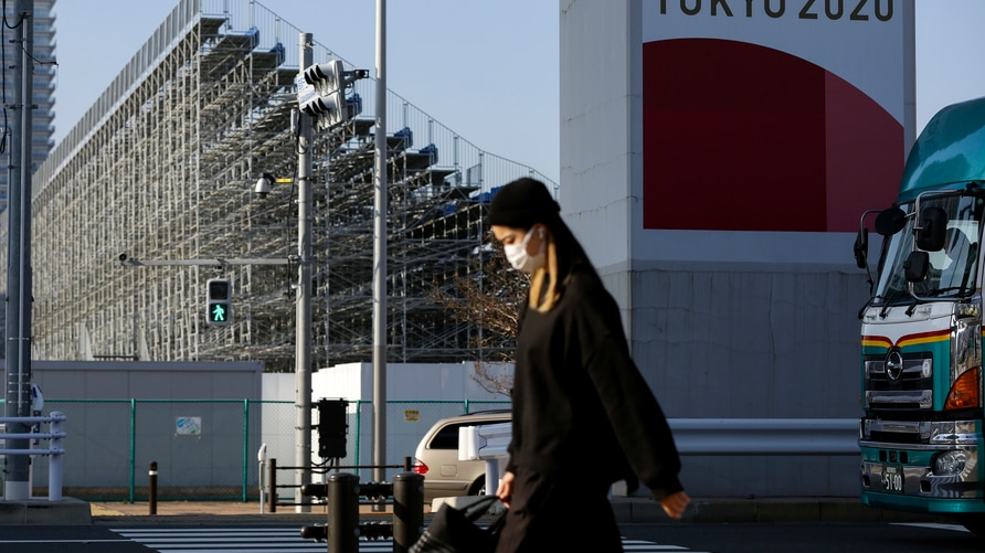 A woman wearing a protective mask passes by the bleachers for the Tokyo 2020 Olympic BMX course Monday, Dec. 7, 2020, in Tokyo…