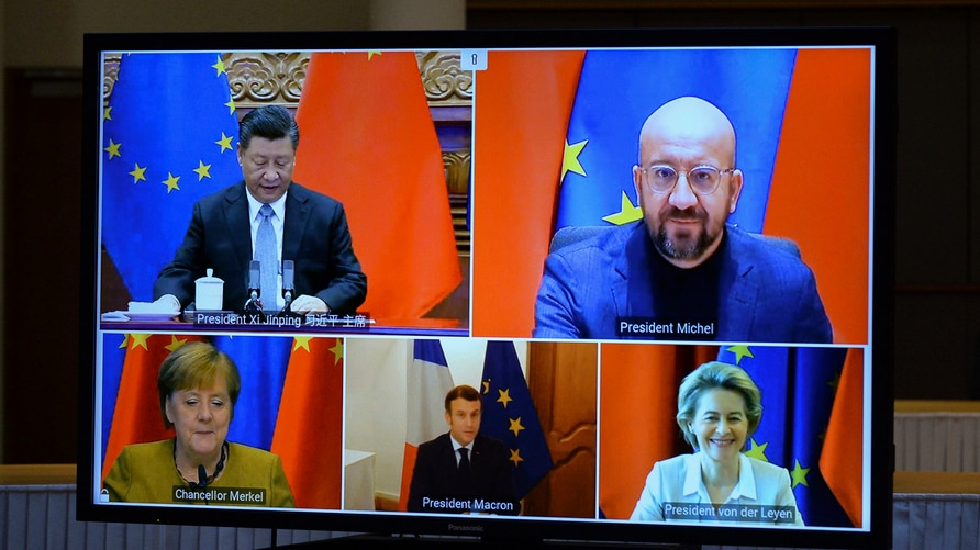 A screen displays live Chinese President Xi Jinping, top left, European Council President Charles Michel, top right, European…