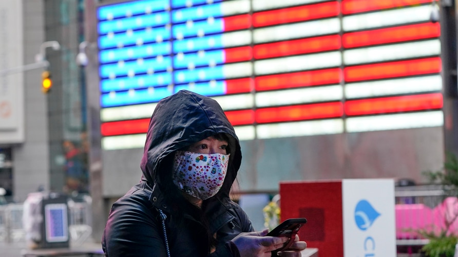 A woman wears a protective mask during the coronavirus pandemic in Times Square Thursday, Dec. 31, 2020, in New York. (AP Photo…