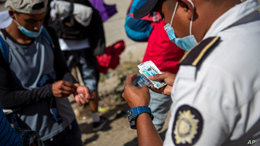 A member of the Guatemalan police checks the ID's of detained Honduran migrants before being sent by bus to El Florido, one of…
