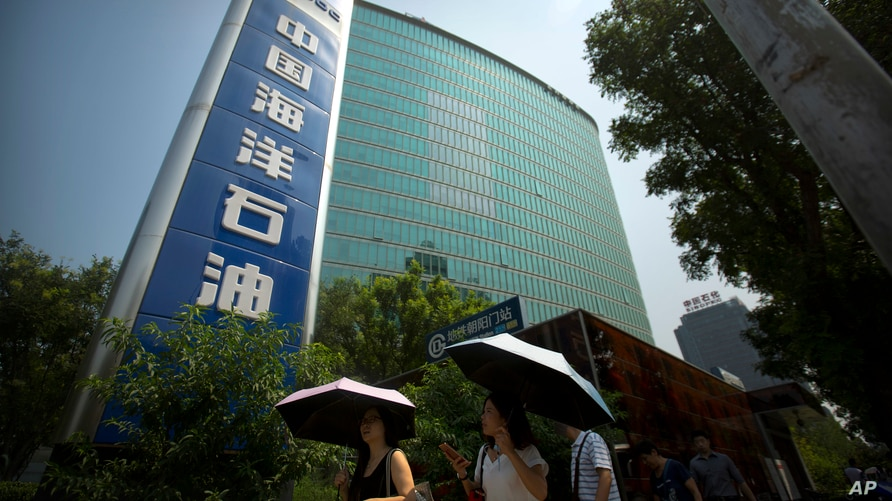 In this Thursday, July 28, 2016 photo, people walk past the headquarters of the China National Offshore Oil Corporation in…