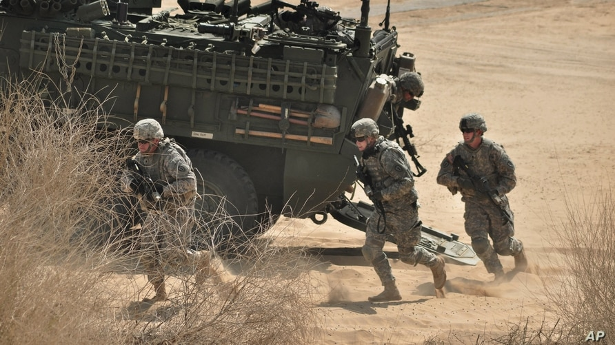 US Army troops run out of a Stryker armored vehicle as they take part in a joint military exercise with Indian Army troops…