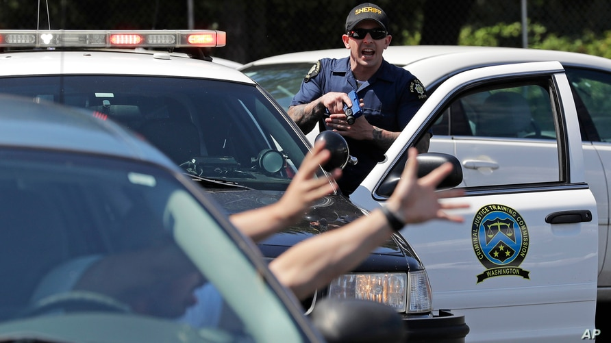In this July 16, 2019, photo, a King County Sheriff's deputy holds a training weapon as he practices a traffic stop during a…