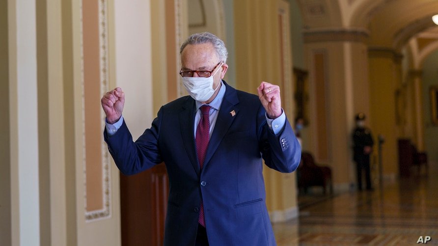 Senate Majority Leader Chuck Schumer, D-N.Y., leaves the chamber just after the Senate narrowly approved a $1.9 trillion COVID…