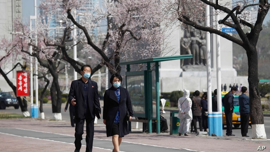 People, wearing face masks, walk in the street in Pyongyang, on Monday, April 5, 2021. (AP Photo/Cha Song Ho)