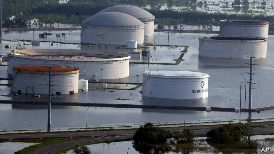 In this aerial photo, holding tanks for Colonial Pipeline Company sit in floodwaters caused Tropical Storm Harvey in Port…