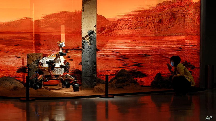 A woman wearing a mask talks on her phone near an exhibition depicting a rover in Mars in Beijing on Friday, May 14, 2021…