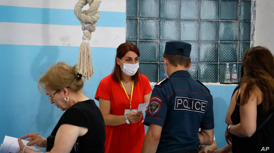 Voters receive their ballot papers at a polling station during a parliamentary election in Yerevan, Armenia, Sunday, June 20,…