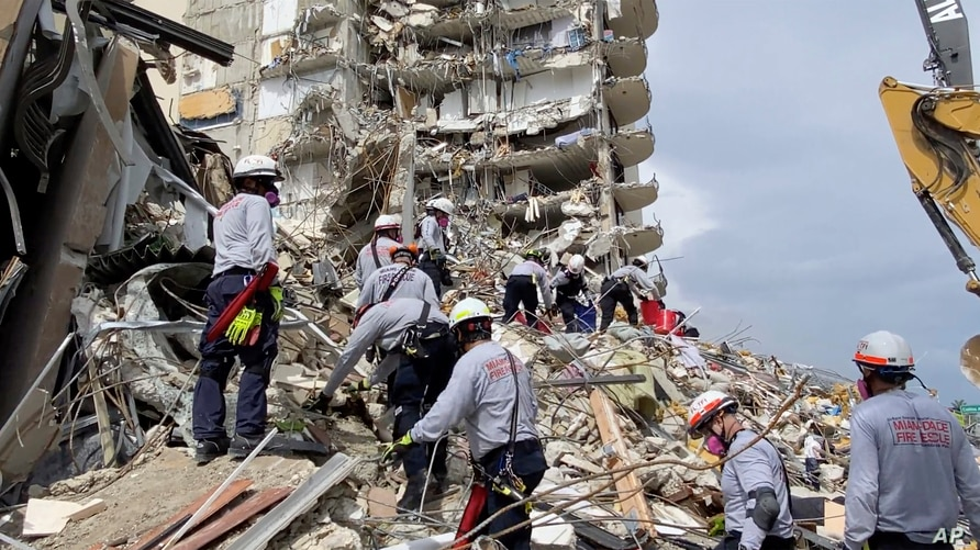 This photo provided by Miami-Dade Fire Rescue, search and rescue personnel search for survivors through the rubble at the…