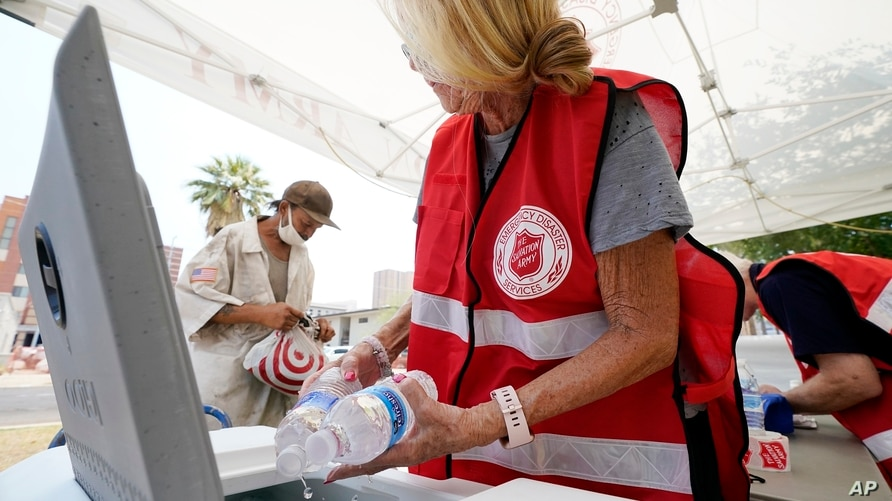 Salvation Army hydration station volunteer Kathleen McAllister, right, hands out water during a heatwave sending temperatures…
