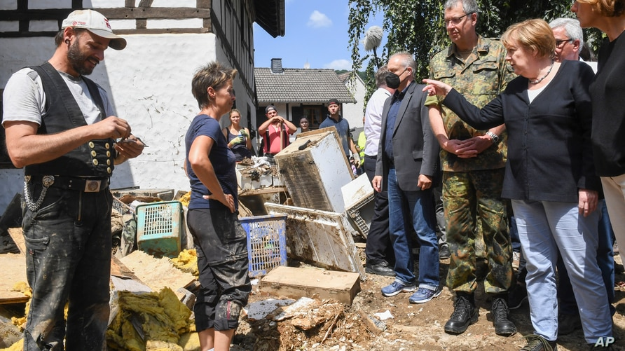 German Chancellor Angela Merkel, right, talks to residents during a visit to the flood-damaged village of Schuld near Bad…