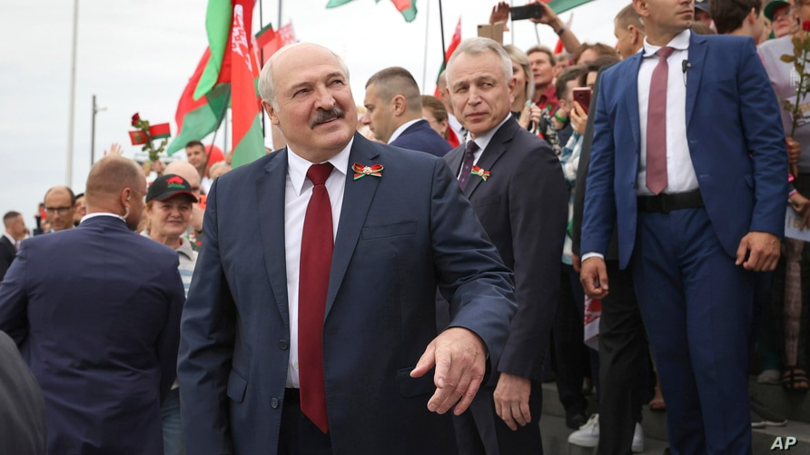 Belarusian President Alexander Lukashenko speaks with people after the wreath laying ceremony at Mound of Glory war memorial…