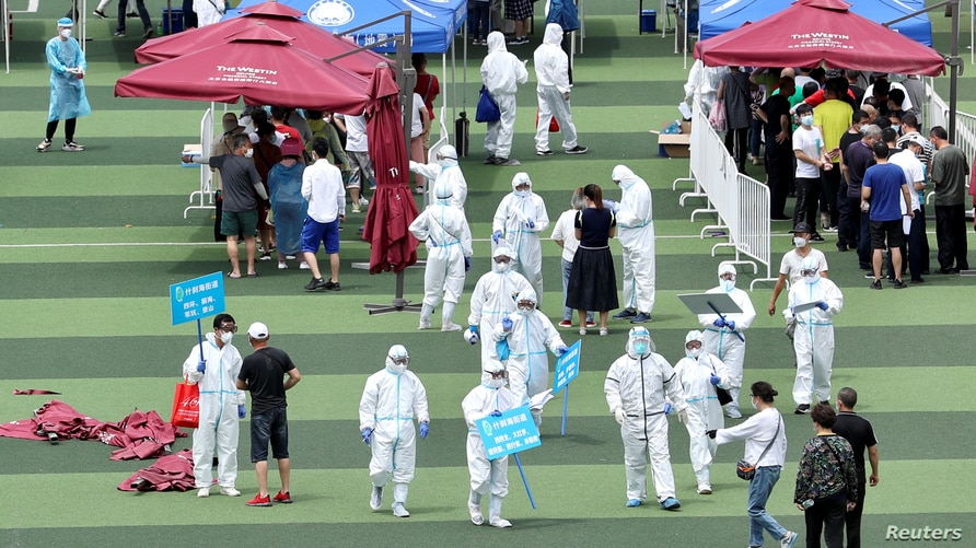 Medical workers help people lining up inside a sports centre for nucleic acid tests in Beijing