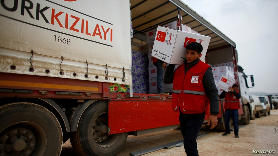 FILE PHOTO: Turkish Red Crescent workers carry humanitarian aid at Kelbit camp in Idlib province