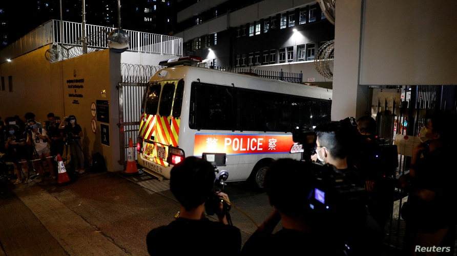 Reporters take pictures and video of a police vehicle driving inside a station where believed members of Hong Kong pro-independence group arrested by the national security unit are held in Hong Kong