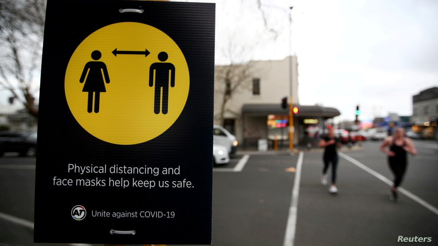 FILE PHOTO: FILE PHOTO: People jog past a social distancing sign in Auckland, New Zealand, August 31, 2020