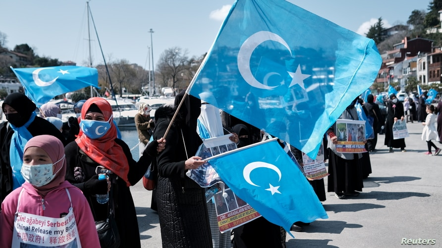 Ethnic Uighur demonstrators wave East Turkestan flags during a protest against China near the Chinese Consulate in Istanbul