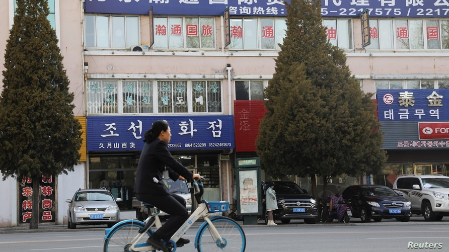 Woman rides a bicycle past shops and companies in Dandong