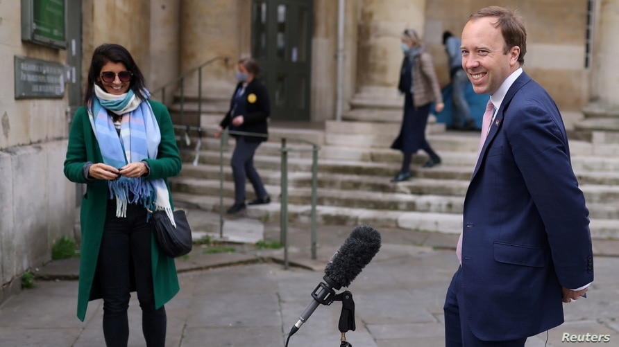 FILE PHOTO: Britain's Health Secretary Hancock smiles during television interview as aide Coladangelo looks on outside BBC's Broadcasting House in London